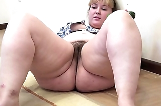 A chunky girl with a hairy pussy masturbates with a cucumber